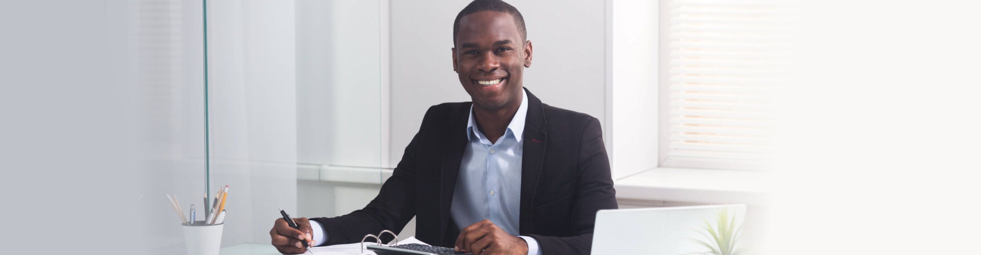man smiling while sitting at his workplace